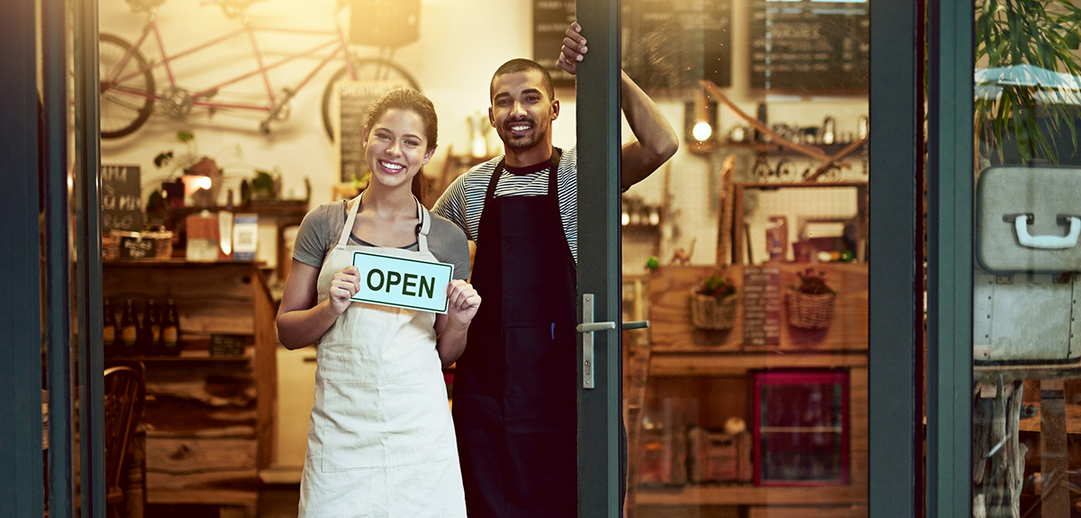 man and woman stand in their shop while the woman holds an open sign