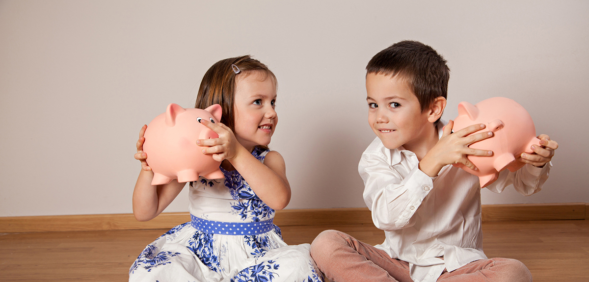two kids sitting on the floor shake piggy banks
