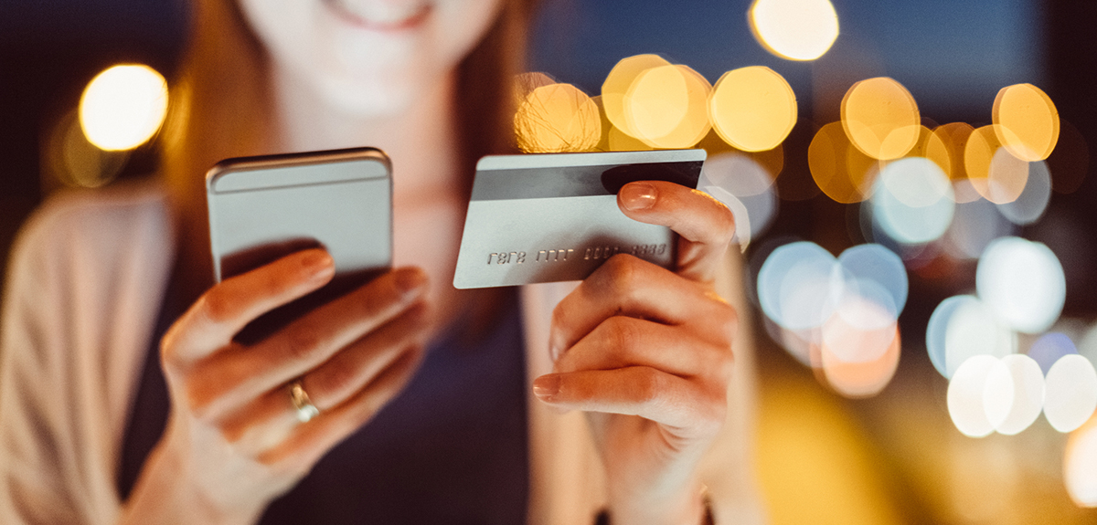 woman holds phone and credit card while smiling