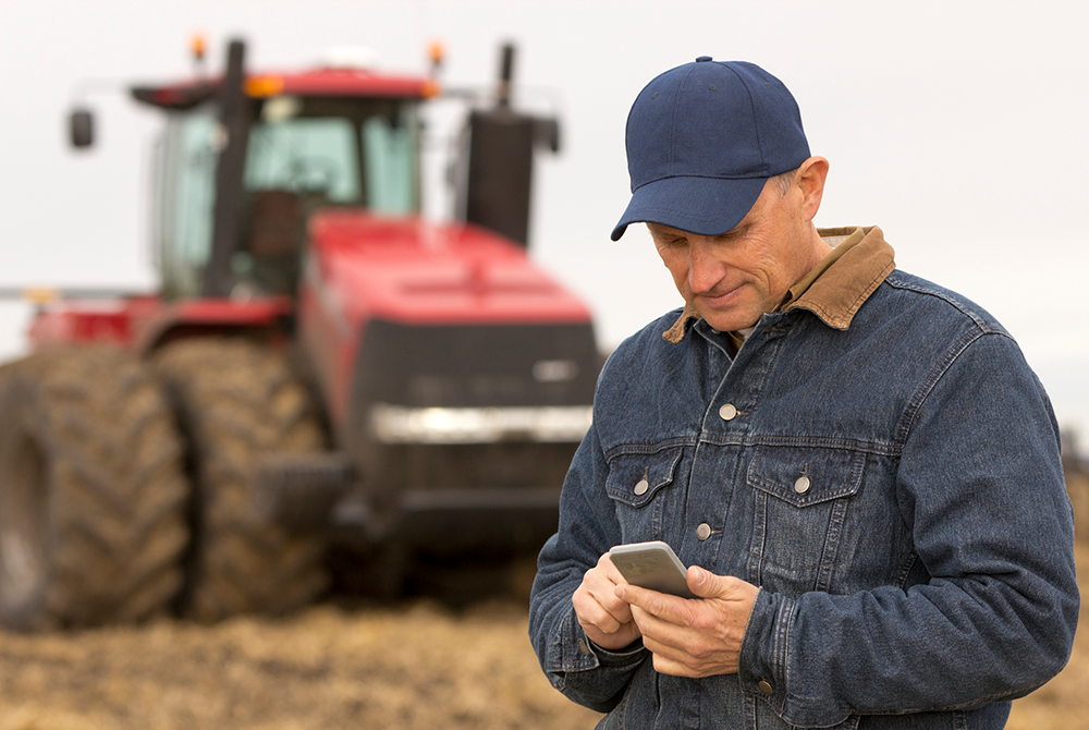 Man looks at phone with tractor in background
