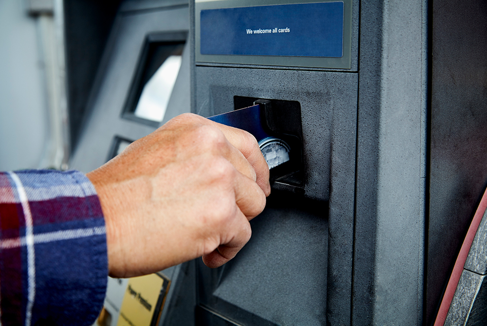 man inserts debit card into atm