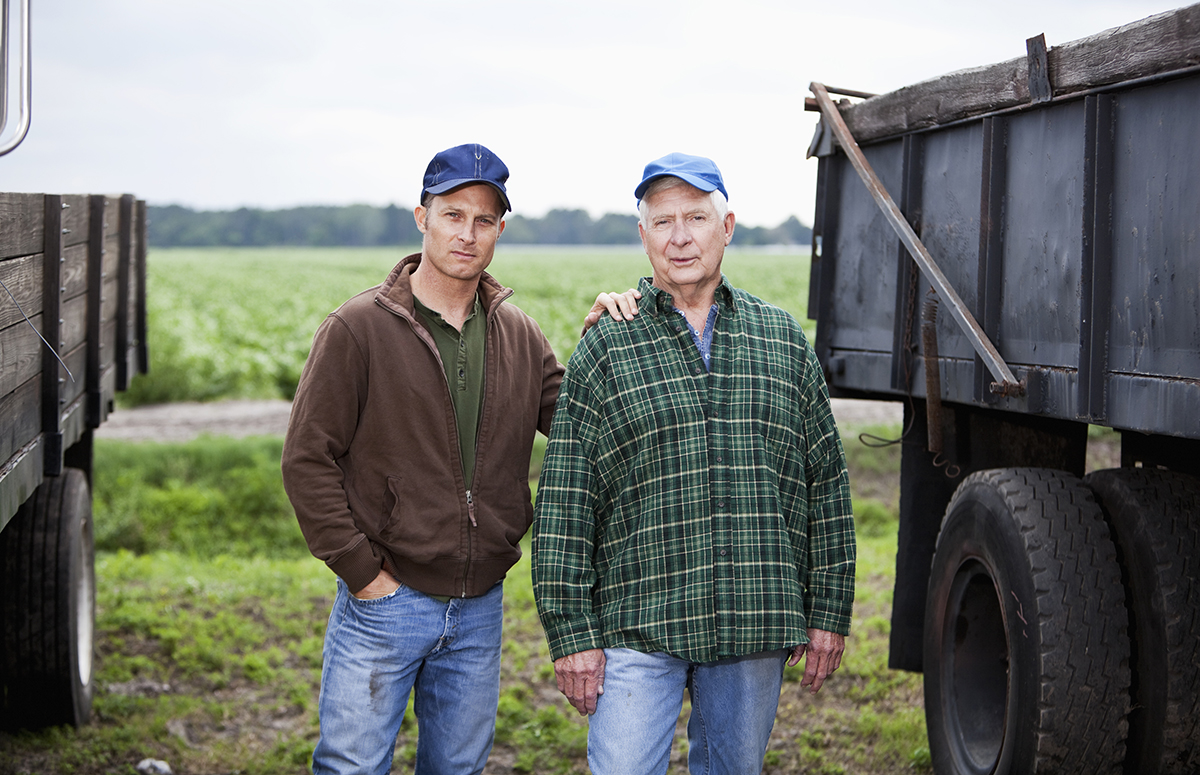 A senior man and his adult son on the family farm standing between two trucks