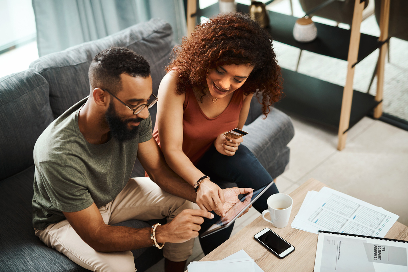couple sitting on couch looking at tablet and holding credit card