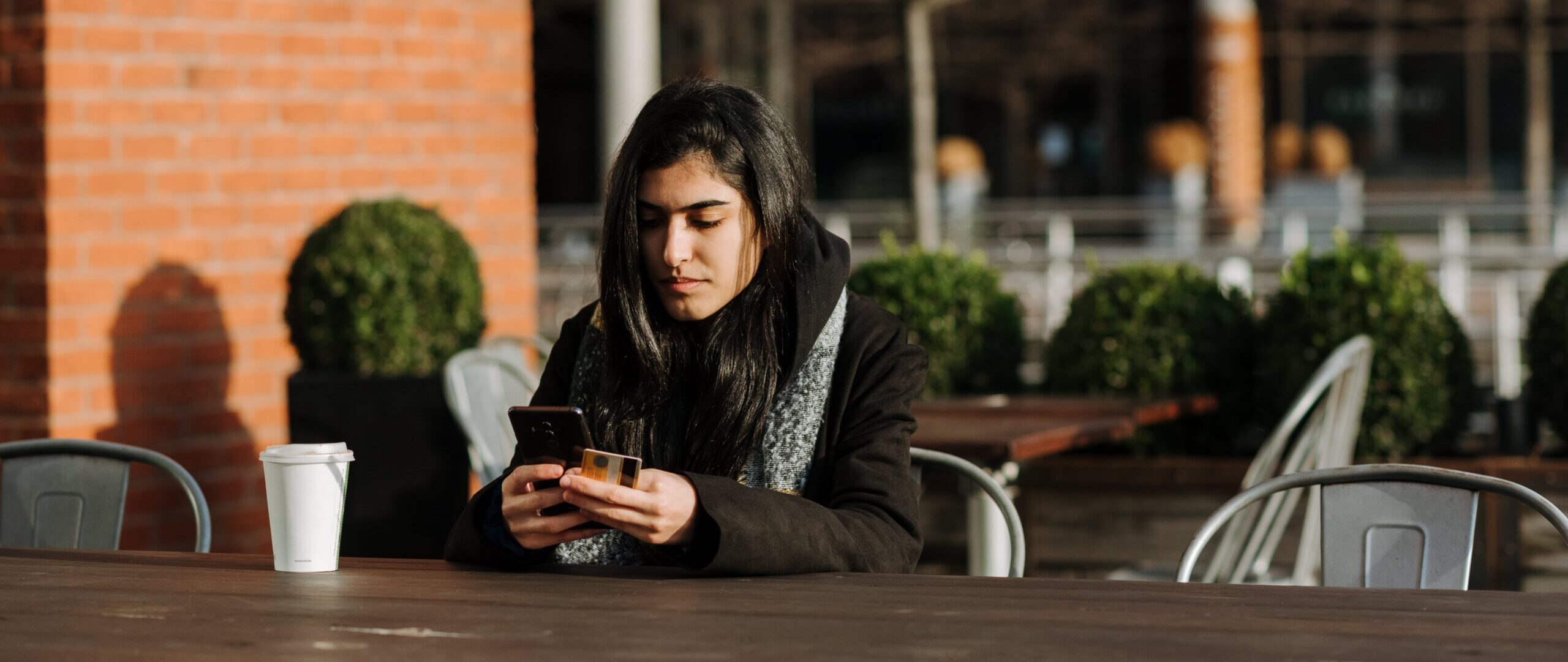 girl sitting outside coffee shop with coffee drink on her phone using the SBR mobile app.