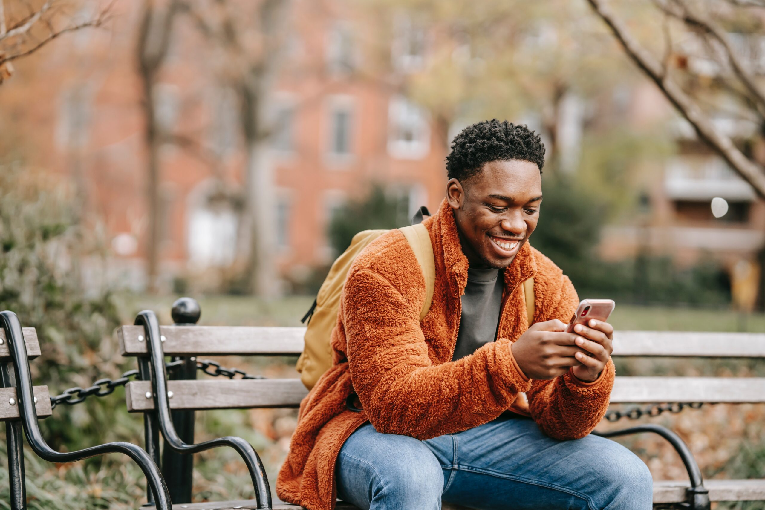 Man smiling at his phone on park bench.