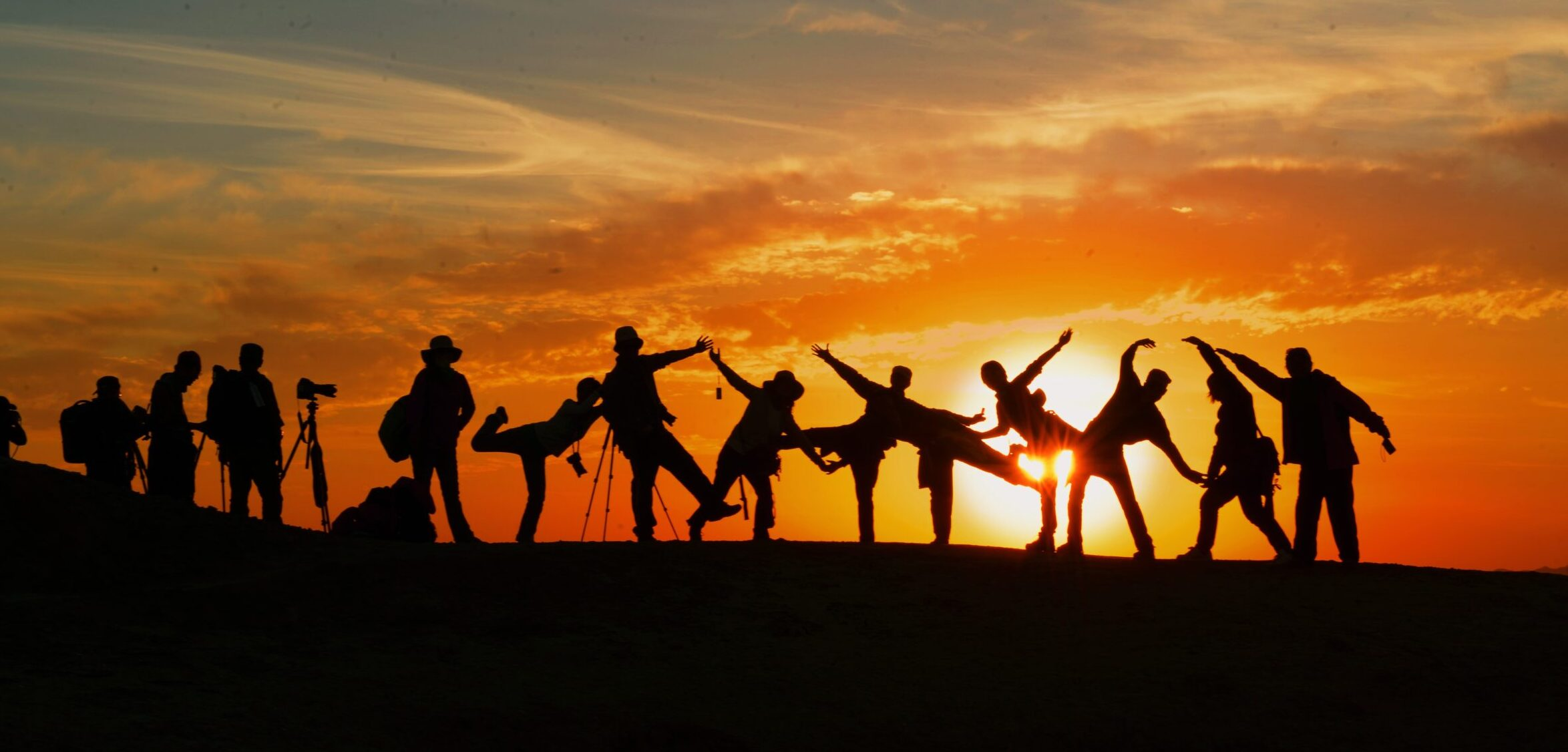 Group of people on a hill at sunset with their silhouettes.